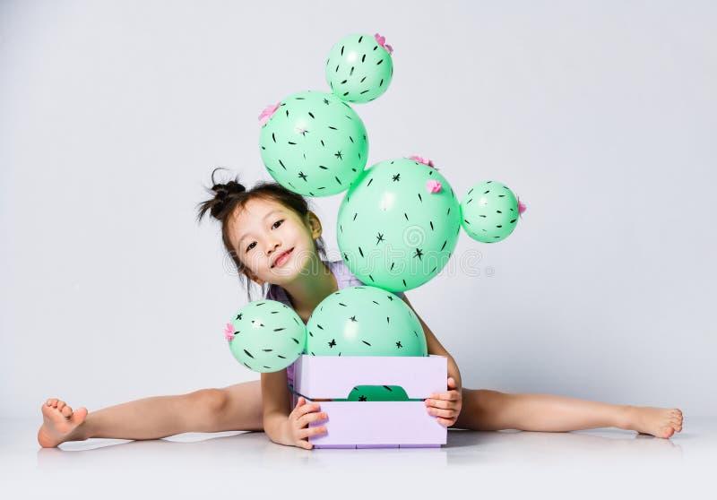 La ragazza asiatica piacevole prendere le spaccature dietro la scatola con il pallone del cactus in, dà una occhiata a fuori e so fotografia stock libera da diritti