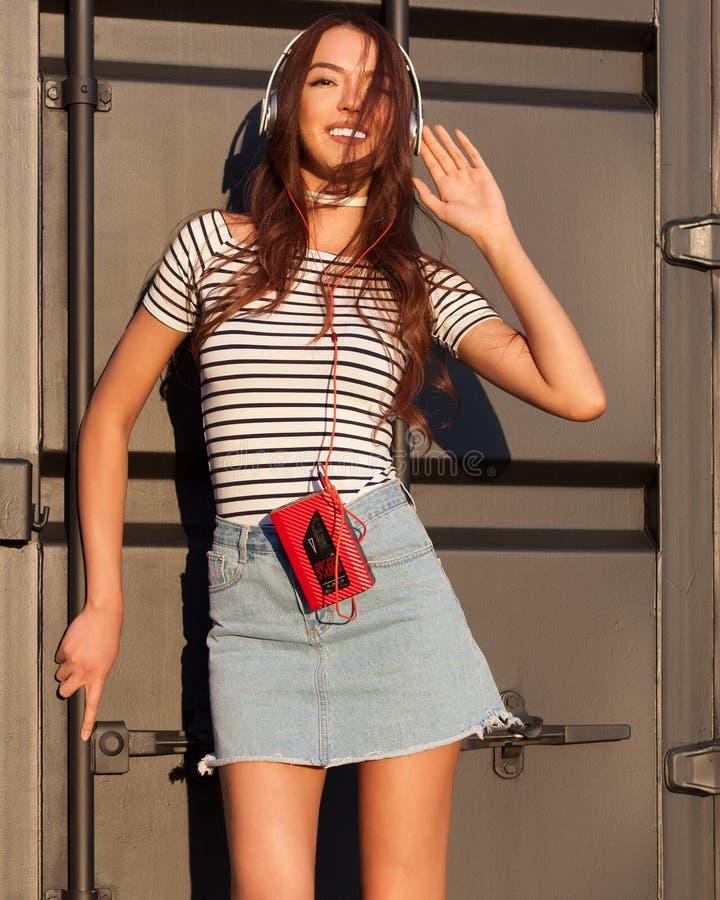 La ragazza asiatica sbalorditiva in un'attrezzatura dell'estate che posa e gode della musica Cuffie e giranastri d'annata rosso A fotografia stock