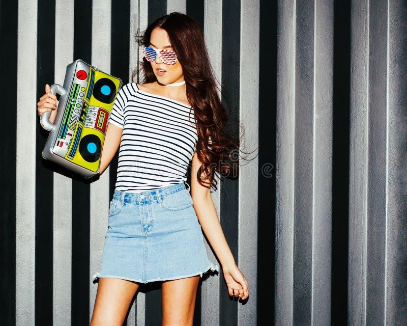La ragazza asiatica sbalorditiva in una gonna del denim gode della musica con un ghettoblaster d'annata Colpo di notte fotografia stock libera da diritti