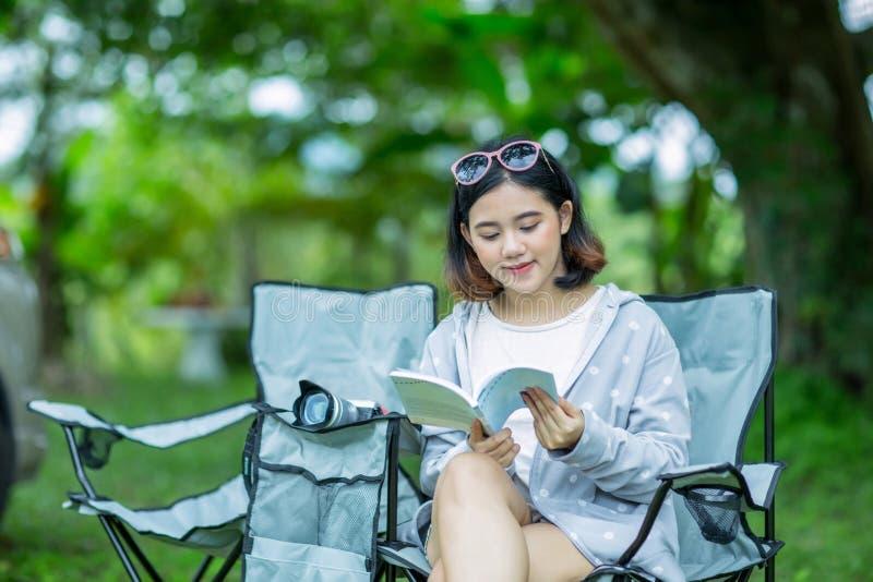 La ragazza asiatica si rilassa con un libro nel giardino immagini stock