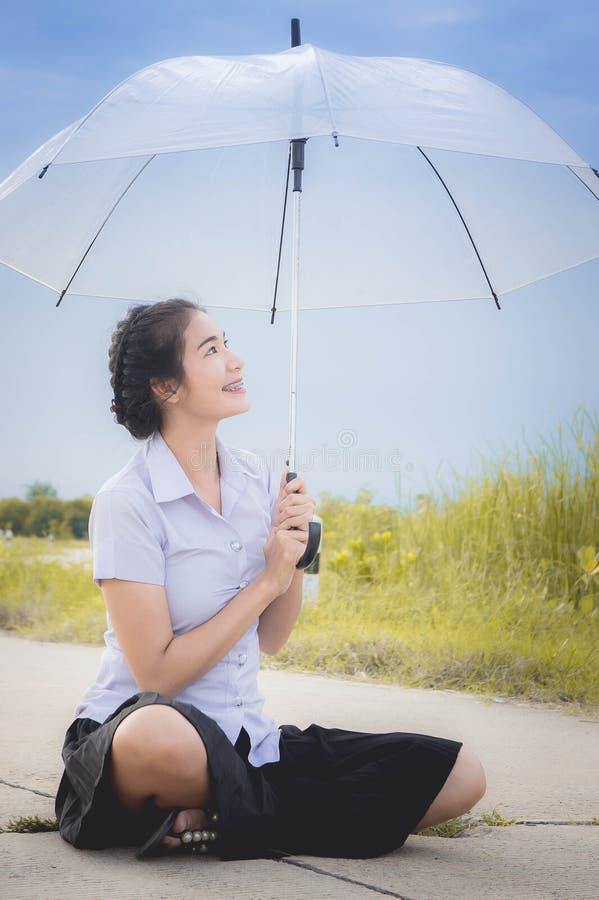 La ragazza asiatica sta sorridendo sulla strada nel prato e nel umbr fotografia stock libera da diritti