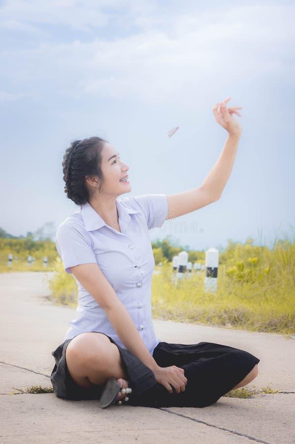 La ragazza asiatica sta sorridendo sulla strada nel prato e nel umbr fotografia stock