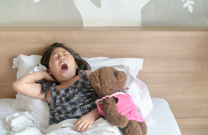 La ragazza asiatica sveglia ed allungando sul letto fotografia stock libera da diritti