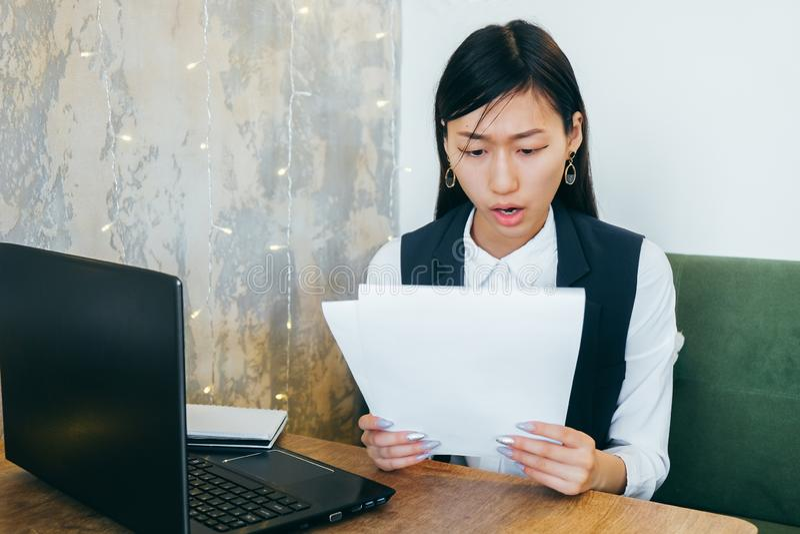 La ragazza asiatica in vestiti leggeri su un fondo grigio imbarazzata guardando i documenti Coworking Sul desktop ? il computer fotografie stock