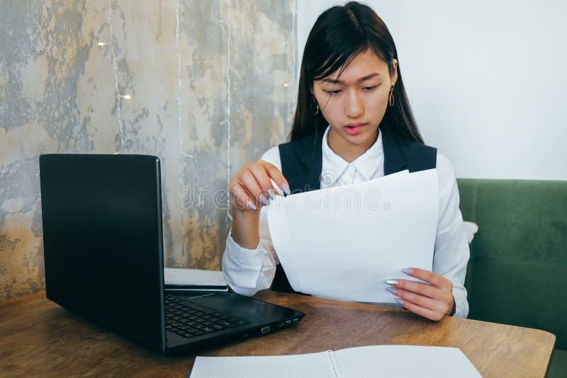 La ragazza asiatica in vestiti leggeri su un fondo grigio imbarazzata guardando i documenti Coworking Sul desktop ? il computer fotografia stock libera da diritti