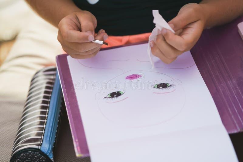 La ragazza assorbe l'album con la spazzola sulla spiaggia fotografie stock libere da diritti