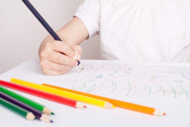 La ragazza assorbe le matite colorate immagini stock