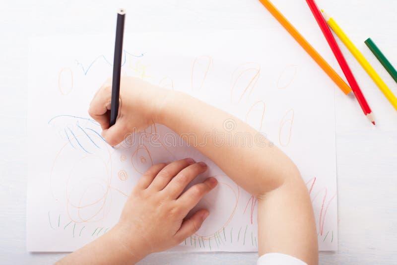 La ragazza assorbe le matite colorate Vista superiore immagini stock