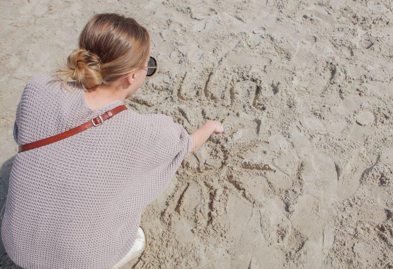 La ragazza assorbe la sabbia vicino al mare Estrae un sole immagini stock