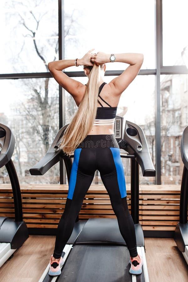 La ragazza atletica con capelli biondi lunghi vestiti negli abiti sportivi sta stando sulla pedana mobile davanti alle finestre d fotografia stock