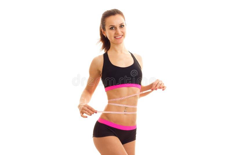 La ragazza atletica sveglia nella cima nera prende il nastro e sorridere di misurazione della vita fotografia stock