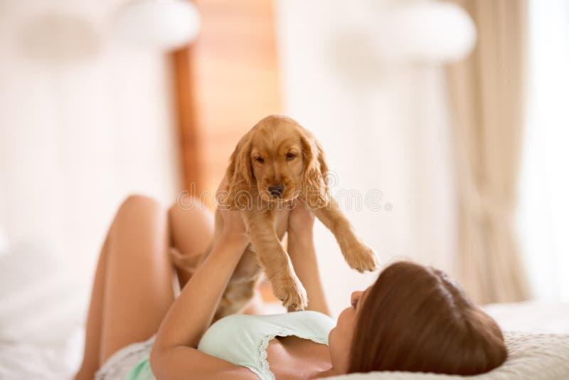 La ragazza attraente ammira la bellezza del suo cucciolo immagine stock libera da diritti