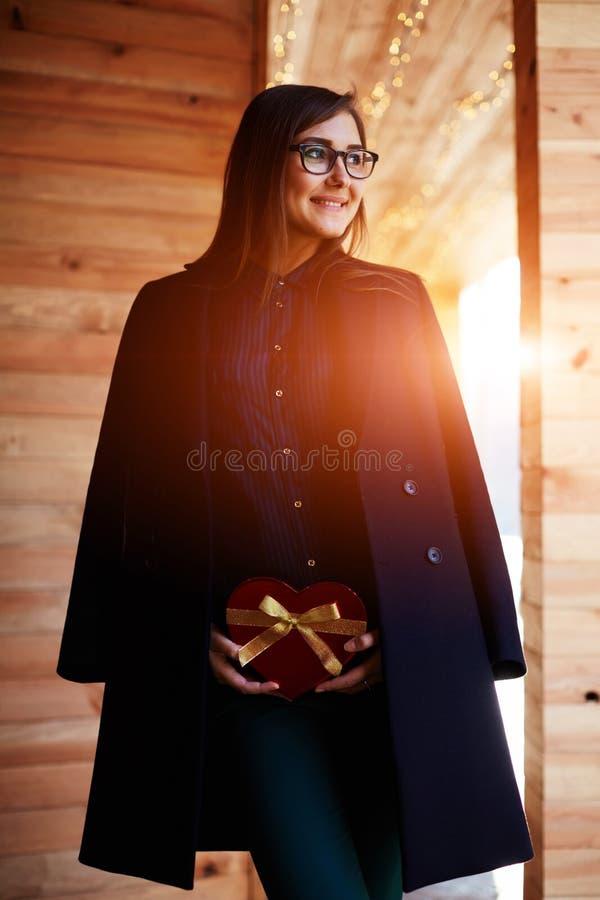 La ragazza attraente che tiene il regalo in forma di cuore ha presentato dal suo marito fotografia stock