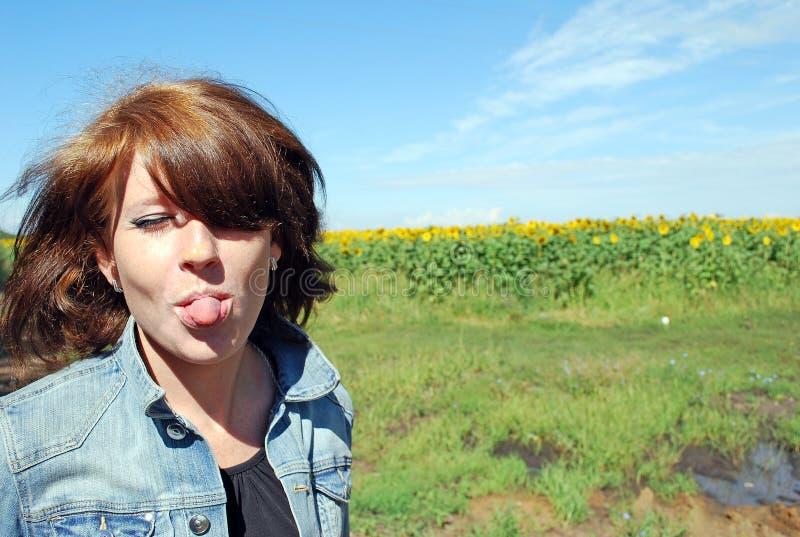 La ragazza attraente, felice mette fuori la lingua contro lo sfondo del campo dei girasoli immagini stock