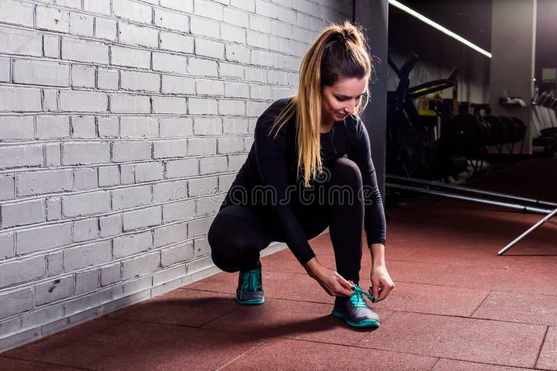 La ragazza attraente lega i pizzi sulle scarpe da tennis fotografia stock