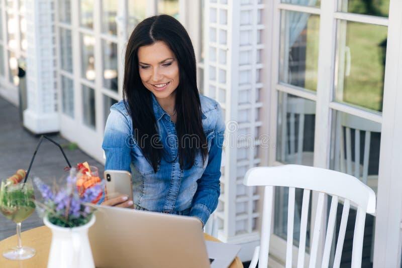 La ragazza attraente si siede in un caffè, legge gli sms sul suo smartphone ed i sorrisi, utilizza il computer portatile per lavo fotografie stock libere da diritti