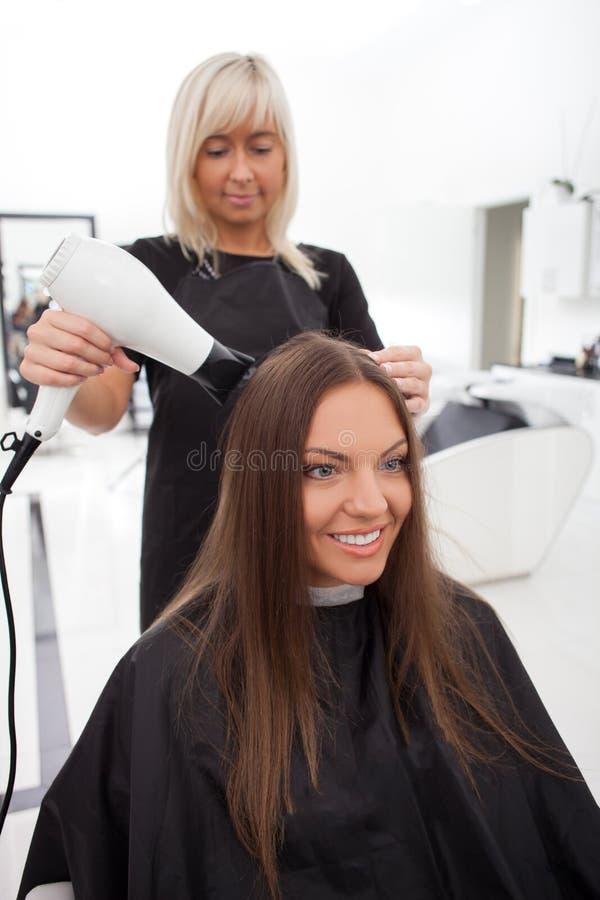 La ragazza attraente sta assistendo ad un salone di bellezza fotografie stock libere da diritti