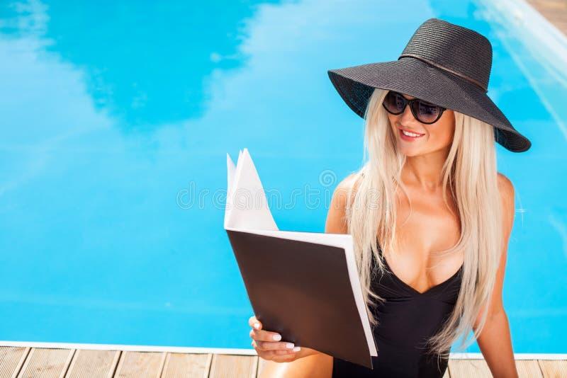 La ragazza attraente sta rilassandosi vicino all'acqua fotografie stock libere da diritti