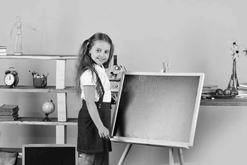 La ragazza in aula sta la lavagna vicina, spazio della copia Scolara con il fronte sorridente vicino allo scaffale per libri con  fotografia stock