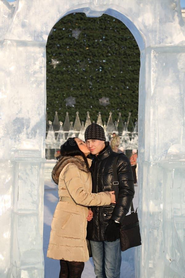 La ragazza bacia il ragazzo nell'arco del ghiaccio vicino al grande albero di Natale fotografie stock libere da diritti