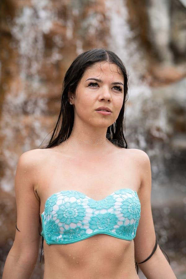La ragazza bagnata in un costume da bagno esamina la distanza Nei precedenti è una roccia e una cascata immagine stock