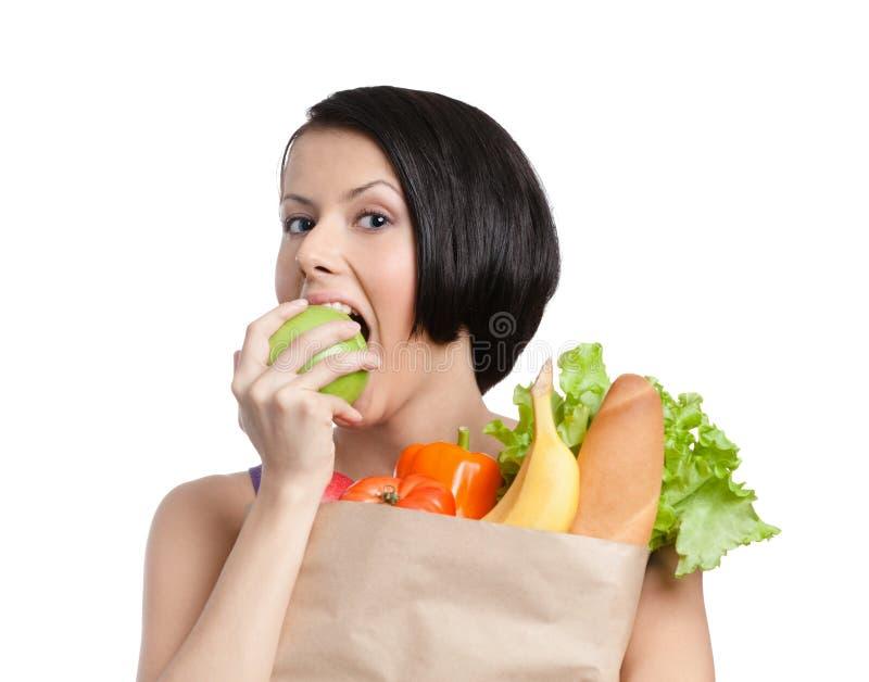 La ragazza bella mangia una mela immagini stock libere da diritti