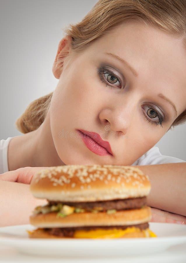 La ragazza bella si siede su una dieta, triste e sull'hamburger fotografie stock libere da diritti