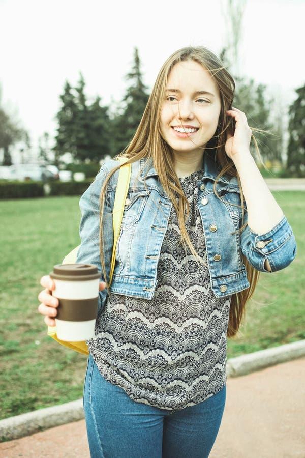 La ragazza beve il caffè dalla tazza riutilizzabile fotografia stock