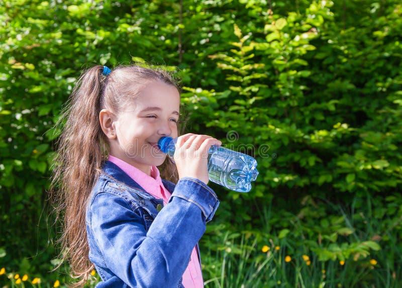 La ragazza beve l'acqua da una bottiglia di plastica