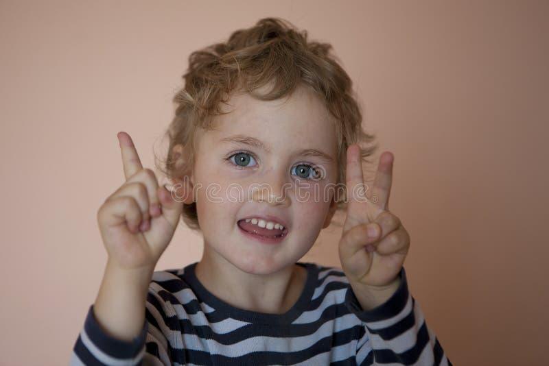 La ragazza bianca allegra con gli occhi azzurri impara contare sulle sue dita fotografia stock