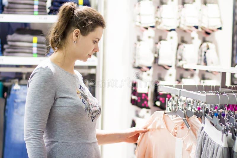La ragazza bianca sceglie i vestiti in boutique fotografie stock