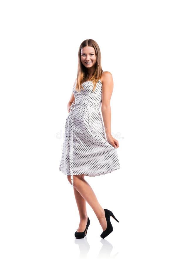 La ragazza in bianco e nero ha punteggiato il vestito, talloni, colpo dello studio, isolat immagine stock libera da diritti