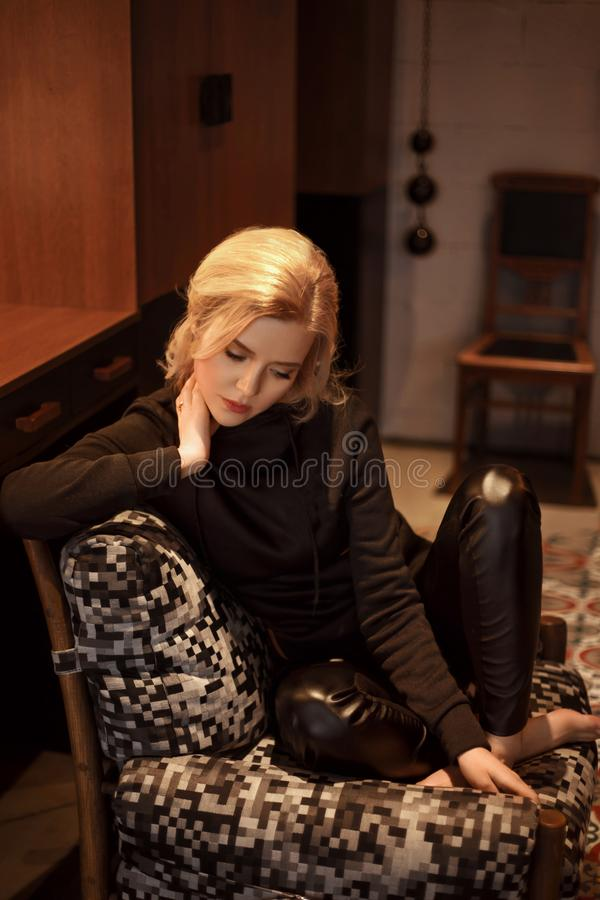 La ragazza bionda è vestita in abbigliamento casual Donna che posa contro il contesto di un interno nello stile del sottotetto Mo fotografie stock