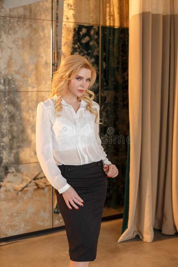 La ragazza bionda è vestita in vestiti dell'ufficio, che seduce con la sua trasparenza Blusa di seta, di bianco e rigoroso nero fotografia stock