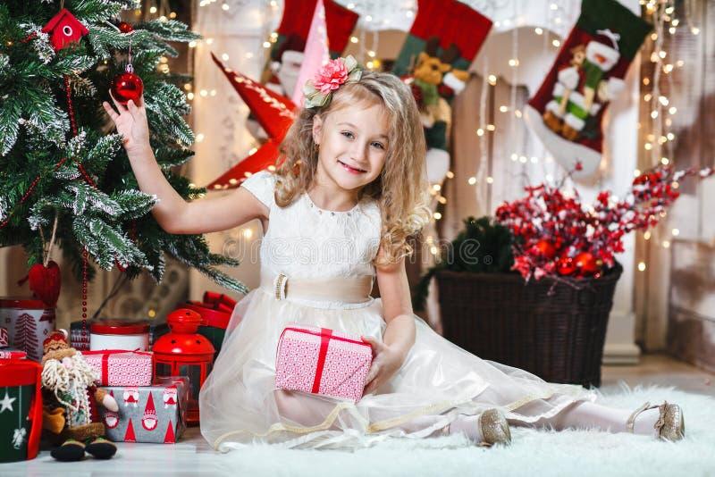 La ragazza bionda abbastanza piccola che sorride con una clip e un vestito beige di capelli del fiore con il presente decora un a immagini stock libere da diritti