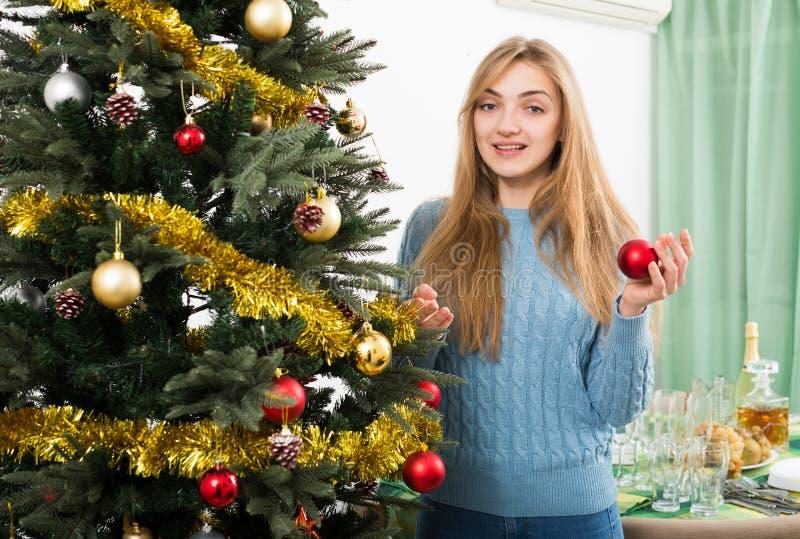 La ragazza bionda allegra con i globi si avvicina all'albero di natale fotografia stock libera da diritti
