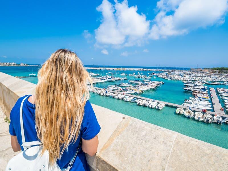 La ragazza bionda ammira il porto di Otranto, Puglia, Italia immagini stock libere da diritti