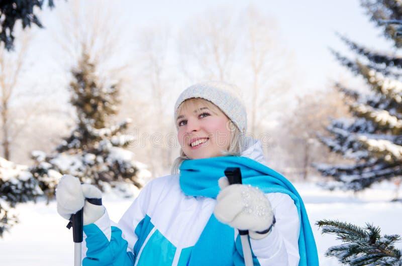 La ragazza bionda attraente con i pali di sci in mani con un sorriso guarda fotografia stock libera da diritti