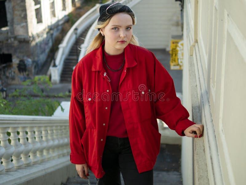 La ragazza bionda attraente dei pantaloni a vita bassa in un rivestimento black hat e rosso tricottato sta stando sulle scale sot fotografie stock