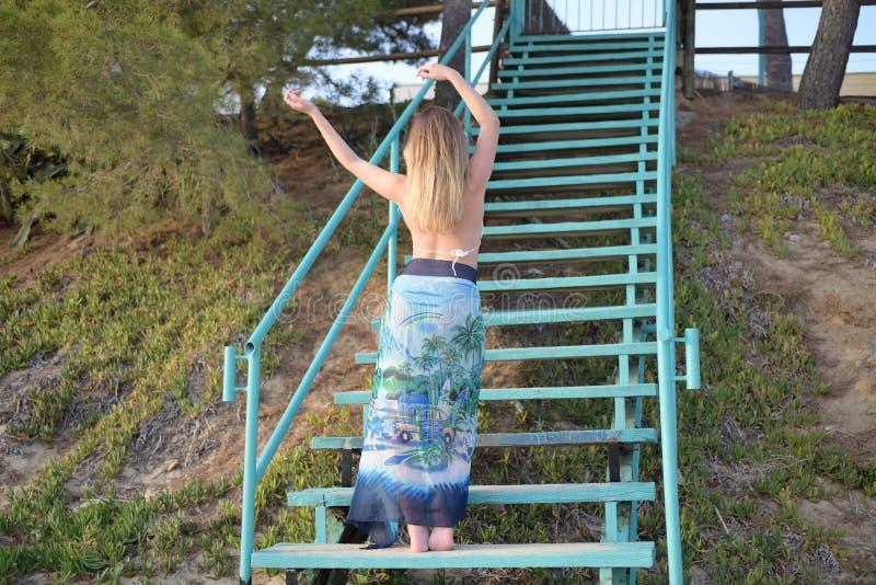 La ragazza bionda balla lentamente sulle scale di nuovo alla macchina fotografica con le armi alzate fotografia stock