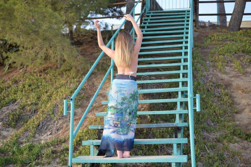 La ragazza bionda balla sensuale sulle scale di nuovo alla macchina fotografica con le armi alzate fotografie stock