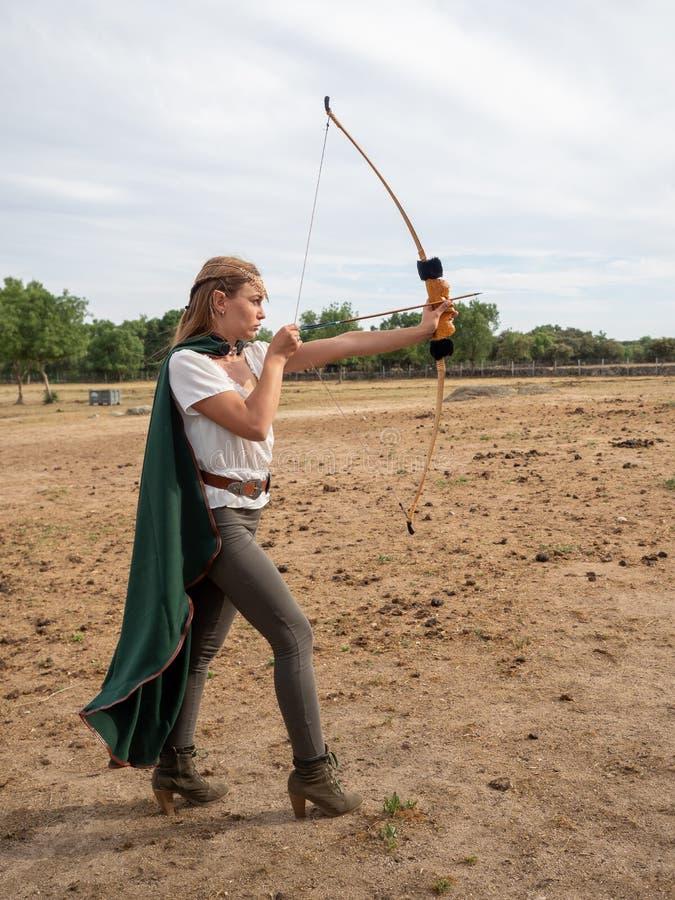 La ragazza bionda con le orecchie dell'elfo posa nel campo con un arco e un capo verde fotografia stock libera da diritti