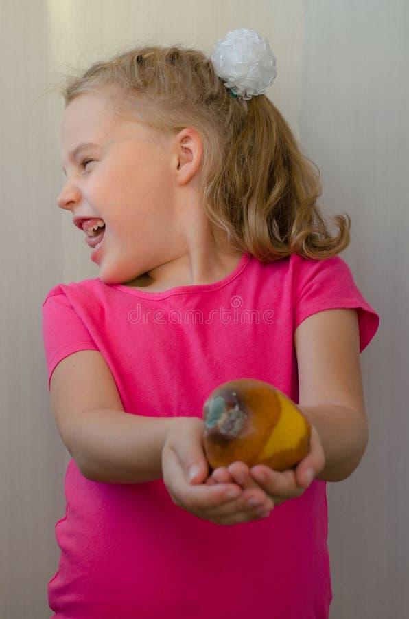 La ragazza bionda con repulsione abbandona la pera marcia fotografia stock