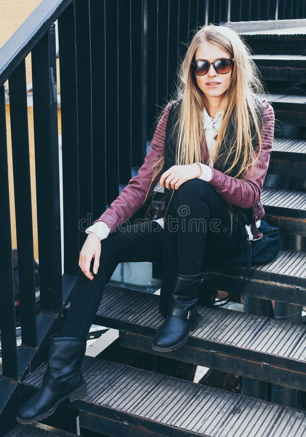 La ragazza bionda dai capelli lunghi si siede in vestiti alla moda ed occhiali da sole sui punti Godere del resto immagine stock libera da diritti