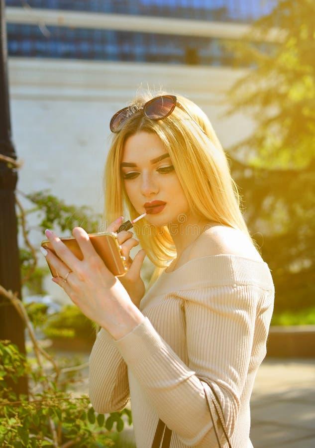 La ragazza bionda elegante in occhiali da sole dipinge le sue labbra con rossetto rosso sui grattacieli Una donna sta applicando  fotografia stock libera da diritti