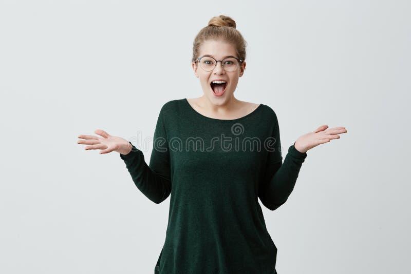 La ragazza bionda felice stupita ha vestito gli occhiali con indifferenza d'uso che esclama nell'eccitazione e che scrolla le spa fotografie stock libere da diritti
