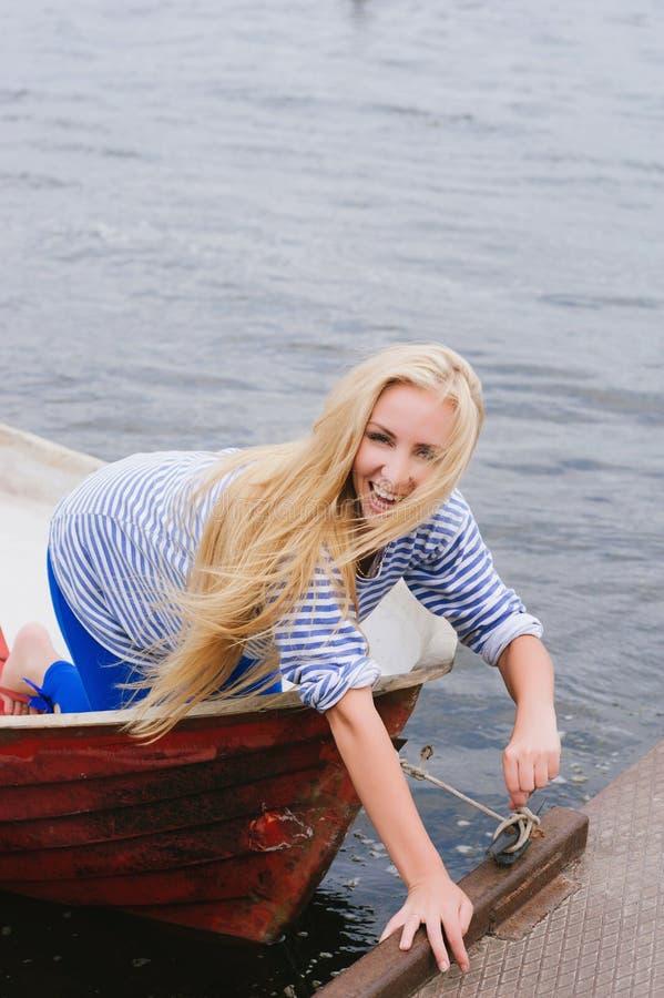 La ragazza bionda lega la barca al pilastro immagini stock