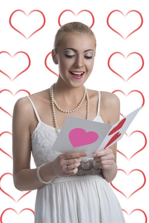 La ragazza bionda legge la cartolina del biglietto di S. Valentino fotografia stock