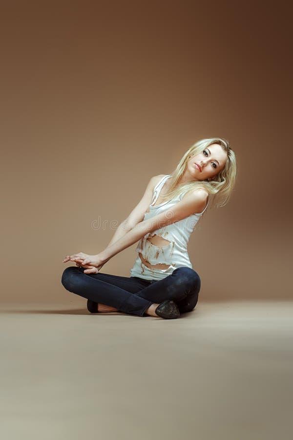 La ragazza bionda molto espressiva in una cima lacerata bianca ed i jeans si siedono sopra fotografie stock