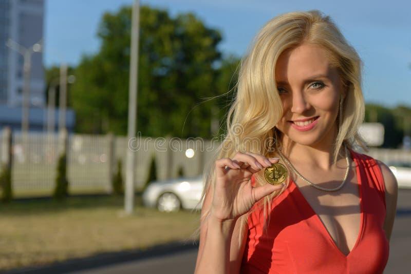 La ragazza bionda sorridente in vestito rosso tiene il bitcoin dorato in due dita immagini stock libere da diritti